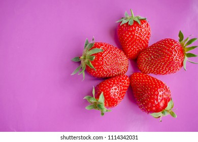 Ripe strawberries close-up on colored backgrounds