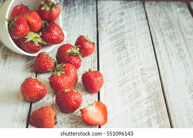 Ripe Strawberries in cup on wooden table  background. Copy space
