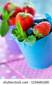 Ripe strawberries and mint leaves in a blue bucket. Healthy eating concept