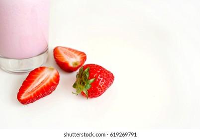 Ripe strawberries next to strawberry milkshake on white background