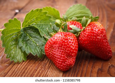 Ripe strawberries and strawberry leaves in a studio on wood.