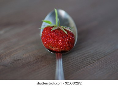 ripe strawberry in a spoon on wooden background