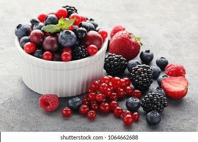 Ripe and sweet berries in bowl on grey wooden table