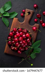Ripe sweet cherries with green leaves in a black bowl on a brown cutting board on a black background. Top view. - Shutterstock ID 1679447677