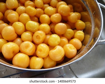 Ripe Sweet Cherries in metal colander with water drops. Close-up of fresh yellow and pink sweet cherries in colander on gray sink surface. Fresh summer background.