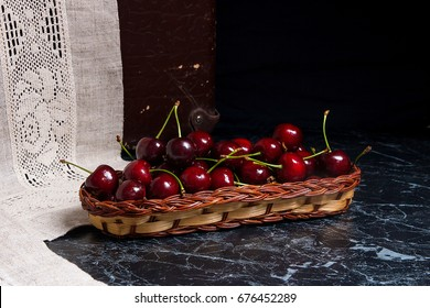 Ripe sweet cherries in yellow wooden basket. Composition in rustic style - organic red sweet cherries in vintage wooden basket on dark marble background. Healthy food concept. Harvest time.