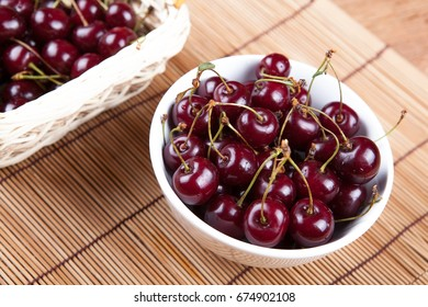 Ripe sweet cherry in a bowl on a bamboo napkin