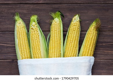 Ripe sweet corn on the cob in a white linen bag on a dark wooden background. Popular grain crops.