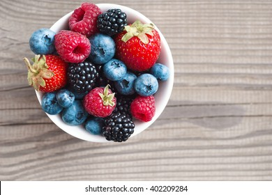 Ripe sweet different berries in bowl. Close up, top view, high resolution product. Harvest Concept