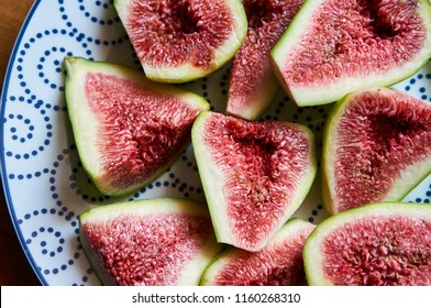 Ripe sweet figs. Figs fruit on a plate close up/macro. Healthy mediterranean fig fruit. Top view. Selective focus on the top figs slice in the bowl. Cut figs. Sliced fresh fruits. Horizontal photo