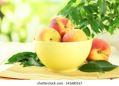 Ripe sweet peaches on table in bowl, outdoors