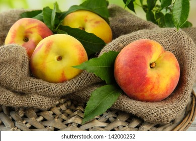 Ripe sweet peaches on wooden table in garden, close up