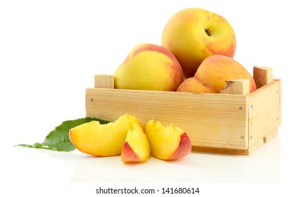 Ripe sweet peaches in wooden crate, isolated on white