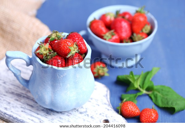 Ripe sweet strawberries in mug  on color wooden background