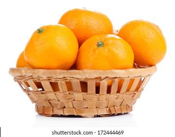 Ripe sweet tangerines in wicker basket, isolated on white