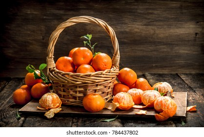 Ripe tangerines in a basket. On a wooden background.