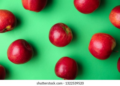 Ripe tasty apples on color background, top view
