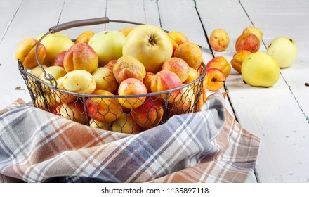 Ripe tasty fresh apricots and apples in  woven metal basket on wooden table in the room