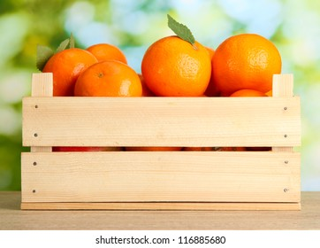Ripe tasty tangerines with leaves in wooden box on table on green background