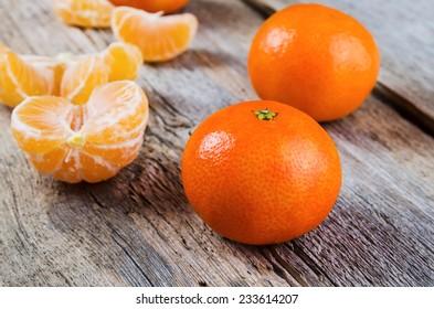 Ripe tasty tangerines on wooden background