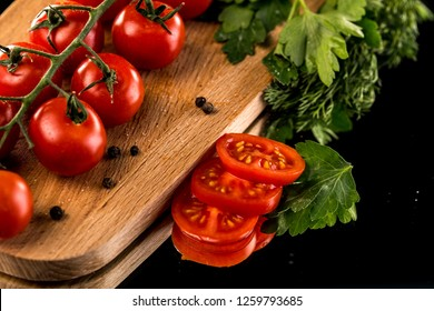 Ripe tomato with water drops on a darck background. Fresh tomatoes on a black isolated background