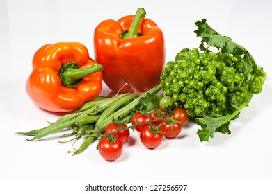 Ripe tomatoes, orange peppers, green beans and  broccoli on white background