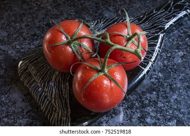 ripe tomatoes with vine on plate