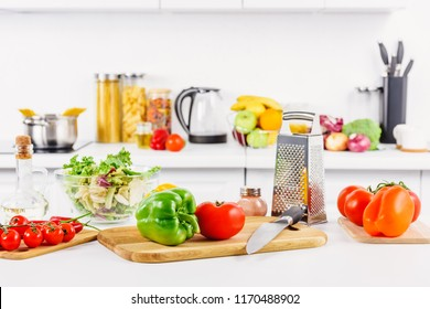 ripe vegetables, knife and grater on table in light kitchen