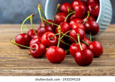 Ripe wet sweet cherries are poured out of the blue bowl on wooden background