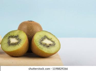 Ripe whole kiwi fruit and half kiwi fruit isolated on wood cutting board.