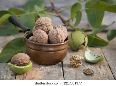 Ripe whole walnuts in vintage bowl and husked nut kernel near walnut branch with leaves and fruits on a wooden background. Walnuts harvest.
