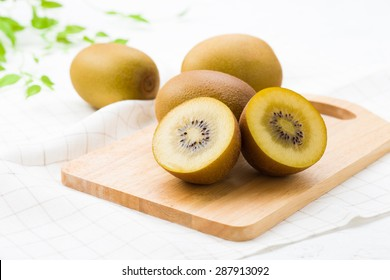 ripe yellow kiwi on a wooden board (sun gold)