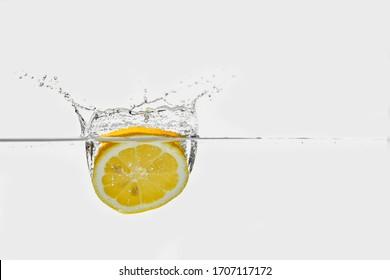 ripe yellow lemon hoop splashing into clear transparent water