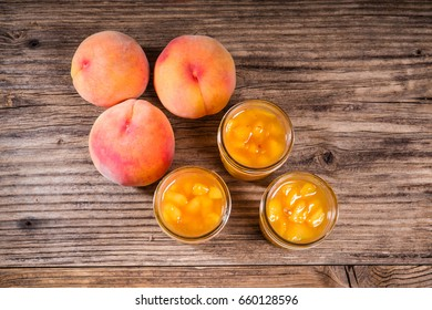 Ripe yellow peaches and jars of preserves or pie filling