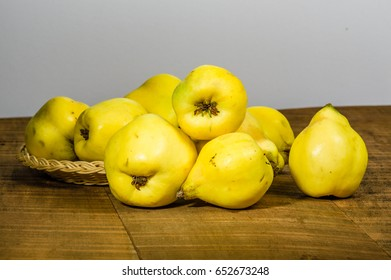 Ripe yellow quince fruit on wooden table