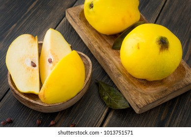 Ripe yellow quince or queen apple fruits and sliced quince lobules with seeds in craft wooden plates on black rustic wooden table close-up