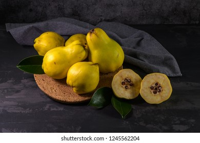 Ripe yellow quinces or queen apple fruits and sliced quince halves with seeds in craft cork plates on black rustic background.
