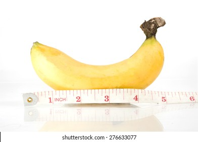 Ripen yellow banana measuring with measurement tape in inches unit, comparable to man penis size as short, small medium, average, long or large size.
