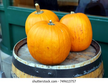 ripened pumpkins on a wooden barrel