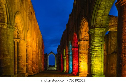 Ripon, Yorkshire, UK. Arched buttresses picked out in colourful lights at dusk in the ancient ruins of Fountains Abbey during Christmas season near Ripon, Yorkshire, UK.