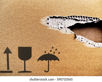 Ripped cardboard; background of torn cardboard; iconic symbols for Keep Dry, This Way Up and Fragile