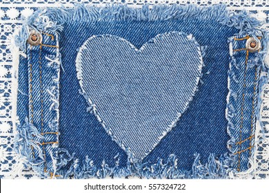Ripped denim heart frame on Destroyed torn denim blue jeans patch pocket  on white lace background. Denim jeans fashion background