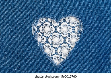 Ripped denim heart frame on Destroyed torn blue jeans on white lace background. Denim jeans fashion background