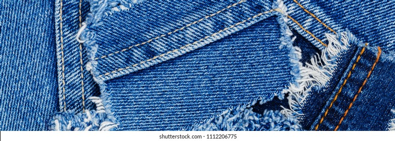 Ripped denim patch  on Destroyed torn denim blue jeans, banner background
