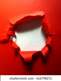 Ripped hole in the red background textured