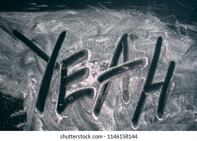 "Ripped powder in the form of the word ""yeah"" on a black table top view"