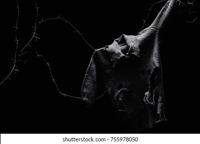 Ripped and torn child shirt on barbed wire on black background, symbol of innocent war victims.