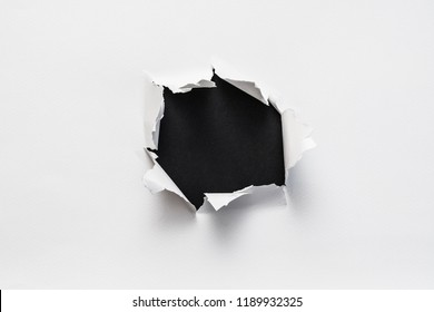 ripped torn white paper showing empty black space. minimalistic background for advertising or text placement.