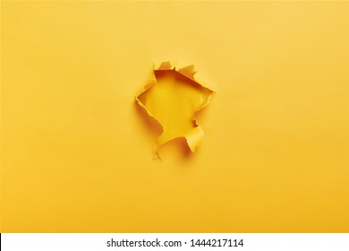 Ripped torn yellow paper with hole in center with no people. Copy space for your promotional content, inscription or advertisement. Blank hole to insert object. Torn colored paper. Abstract shot.