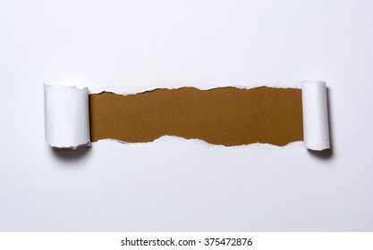 Ripped white paper with curled edges. Different colors under the white paper